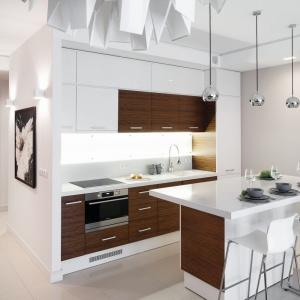 Aby przebić sterylność bieli w kuchni, architekt sięgnęła po akcenty w kolorze orzecha modyfikowanego. Naturalny fornir zdobi część frontów kuchennych. Kolor został również powtórzony na drzwiach w przedpokoju. Projekt: Małgorzata Galewska. Fot. Bartosz Jarosz.