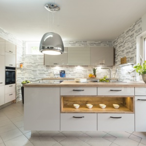 Białe fronty lakierowane na wysoki połysk optycznie powiększają kuchnię. Chłód bieli doskonale równoważą drewniane elementy. Fot. Max Kuchnie.
