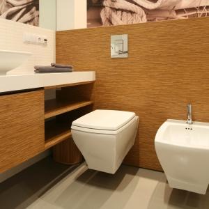Łazienka jest zaplanowana z myślą o jak najwyższej ergonomii rozwiązań. Ponieważ pomieszczenie jest wąskie, półki przy sedesie są otwarte - w ten sposób wyeliminowano konieczność niewygodnego otwierania. Projekt: Małgorzata Galewska. Fot. Bartosz Jarosz.