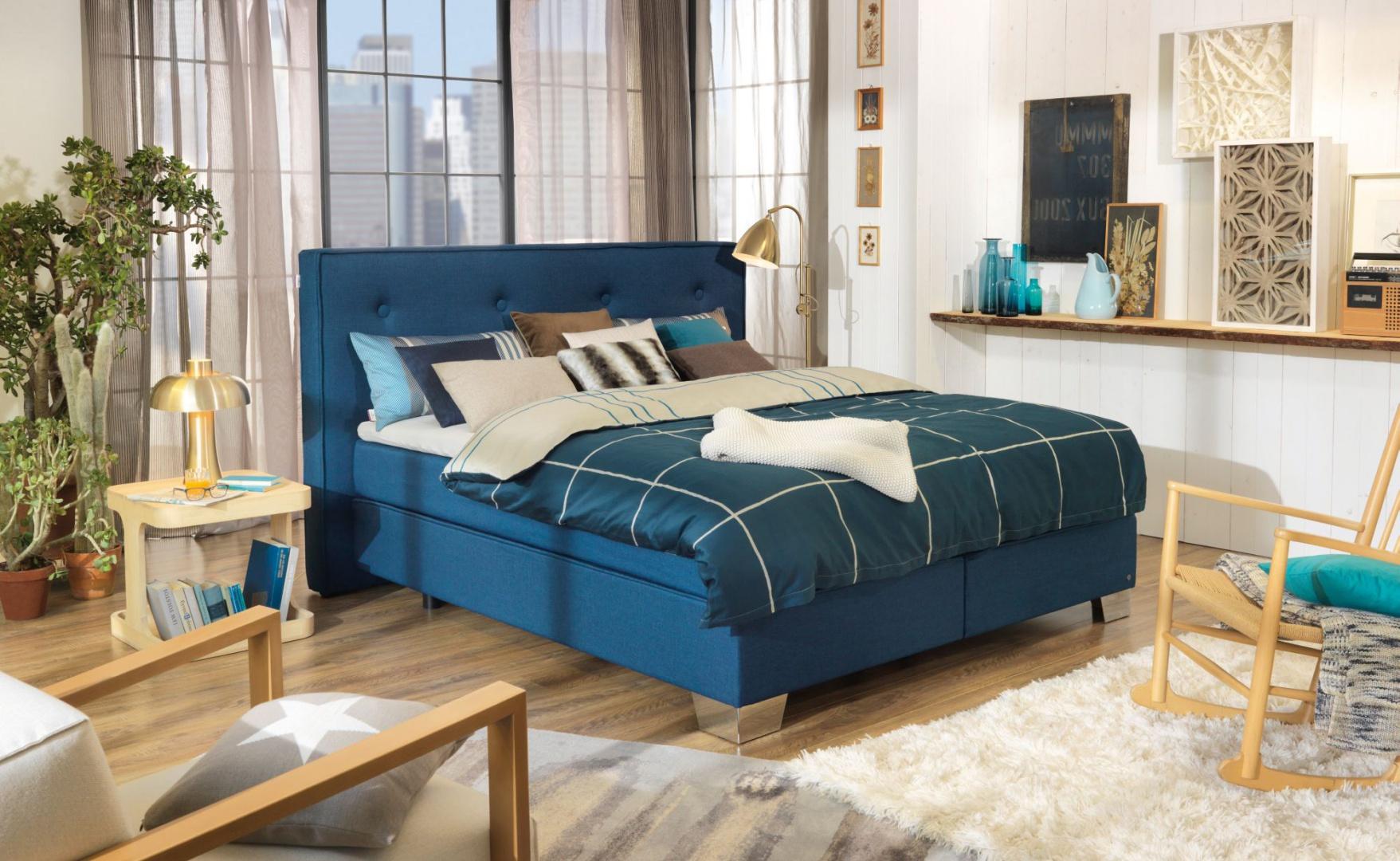 Modna sypialnia to kontrastowe zestawienia. Miękkie, tapicerowane łóżko pięknie komponuje się z drewnianym stolikiem nocnym oraz podłogą. Fot. Tom Tailor.