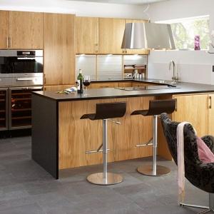 Ta kuchnia to połączenie klasyki z nowoczesnym minimalizmem. Gładkie, proste fronty wieńczą klasyczne, metalowe uchwyty. Solidne meble w kolorze drewna wieńczy czarny blat. Fot. Ballingslov.