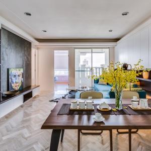 Sercem mieszkania jest otwarta strefa dzienna, którą spaja parkiet ułożony w klasyczną jodełkę oraz długa zabudowa poprowadzona przez ścianę. Projekt: Archlin Studio.