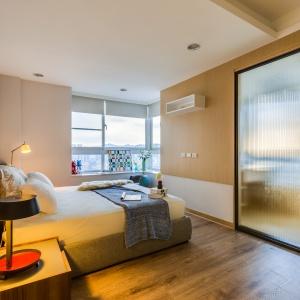 Sypialnię małżeńską od łazienki oddzielają szklane drzwi, które pozwalają na swobodną wędrówkę światła pomiędzy pomieszczeniami. Projekt: Archlin Studio.