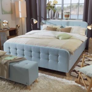 Łóżko tapicerowane miękką tkaniną w pastelowym odcieniu oraz ława wnoszą do wnętrza ciepły wygląd i przytulny charakter. Fot. Tom Tailor.