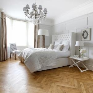 Wysoki zagłówek sprawia, że wnętrze nabiera eleganckiego wyglądu. Całość podkreśla stylowy żyrandol. Fot. Sweetpea & Willow.