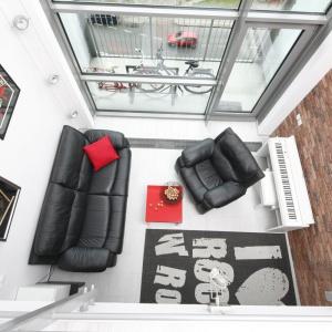 Wyposażenie salonu ograniczono do minimum: znalazły się w nim mięsista sofa i fotel dla komfortowego wypoczynku oraz białe pianino, przy którym właścicielka realizuje swoje pasje. Projekt: Monika Olejnik. Fot. Bartosz Jarosz.
