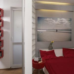 Sypialnia utrzymana w biało-szaro-czerwonej tonacji. Przestrzenny obraz zawieszony nad łóżkiem, wizualnie dodaje wnętrzu przestrzeni. Projekt: Magda Olszewska. Fot. Bartosz Jarosz.