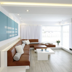 Przestronny salon urządzono w nowoczesnej konwencji. Minimalistyczny wystrój podkreśla skórzana sofa modułowa. Projekt: Dominik Respondek.