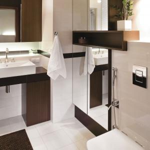 Duże lustra dwukrotnie powiększają łazienkę. Za nimi ukryta jest szafa łazienkowa. Projekt: Magdalena Kuklińska. Fot. Bartosz Jarosz.