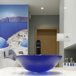 Bardzo ciasna łazienka powiększona przez ogromne lustro bez ram. Odbijająca się w nim fototapeta stwarza złudzenie rzeczywistej przestrzeni. Projekt: Ewa Para. Fot. Bartosz Jarosz.