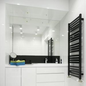 Łazienkę urządzono nowocześnie, w czerni i bieli. Połyskujące powierzchnie okładzin ceramicznych oraz luster optycznie powiększają przestrzeń i dodają szyku. Projekt: Małgorzata Galewska. Fot. Bartosz Jarosz.