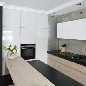 """Modna kuchnia w kolorach ziemi została przebita kolorystycznie pojedynczym rzędem górnych szafek w białym połysku oraz harmonizującą z nimi wysoką zabudową, która """"udaje"""" ścianę. Projekt: Magdalena Smyk. Fot. Bartosz Jarosz."""