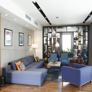 Mieszkanie jest eleganckie inowoczesne, ale nie brakuje także elementów stylu loft, takich jak industrialna lampa, czy oryginalne betonowe płyty na ścianie zakanapą, które odpowiadają za klimat wnętrza. Projekt: Monika i Adam Bronikowscy. Fot. Bartosz Jarosz.