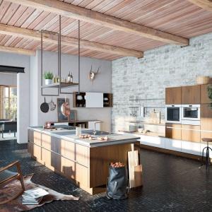 W tej kuchni meble są nowoczesne, ale utrzymane w kolorze drewna, co pozwala im harmonizować z drewnianym sufitem, podtrzymującymi go belkami oraz wyblakłą cegłą na ścianach. Całość tworzy miks tradycji z nowoczesnością. Fot. Wellmann.