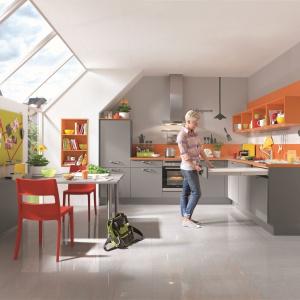 Kuchnia w szarym kolorze pięknie ożywiają elementy w pomarańczowym kolorze. Całość doskonale doświetlają okna dachowe. Fot. Nobilia.