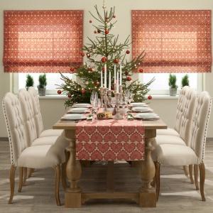 Czerwień do aranżacji stołu można wprowadzić za pomocą tekstyliów. Bieżnik z czerwonym wzorem poprowadzony na nagim stole dodaje mu przytulności i harmonizuje z roletami i czerwonymi bombkami na choince. Fot. Dekoria.