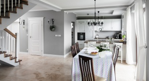 Komfortowa, rodzinna przestrzeń: kuchnia otwarta na salon z kominkiem oraz duża jadalnia.Stylowe wnętrze ubrano w biel oraz szarość.