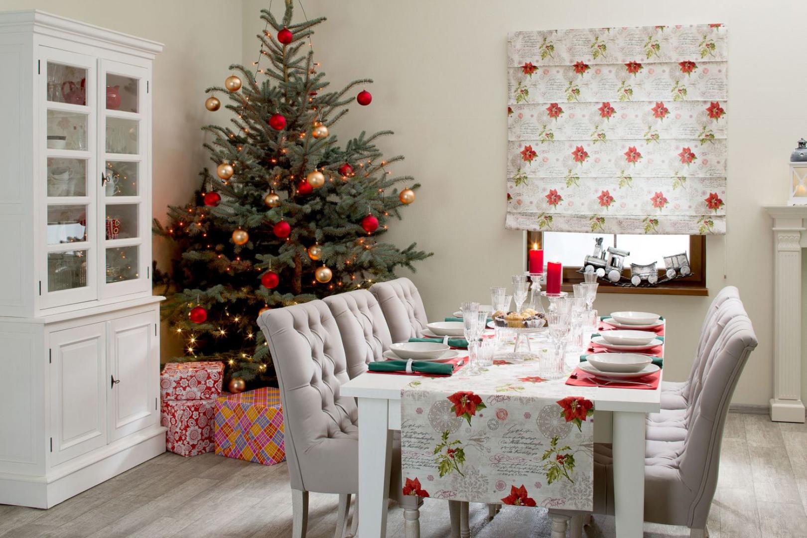 Do świątecznego wystroju jadalni pasują nie tylko typowo świąteczne motywy. Również obrus z kwiecistym wzorem wpisze się w klimat świąt, jeśli utrzymamy go w kolorystyce typowo świątecznej. Czerwień i choinkowa zieleń będą jak znalazł. Fot. Dekoria.