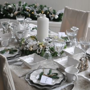 Piękna, niesamowicie elegancka aranżacja stołu. Białe i szare talerze oraz miseczki z delikatnie falującymi brzegami towarzyszą kieliszkom o nowoczesnej formie (również subtelnie przywodzącej na myśl fale). Całości dopełnia haftowany obrus w kolorze złamanej bieli oraz gałązki świerku. Fot. Tendom.pl