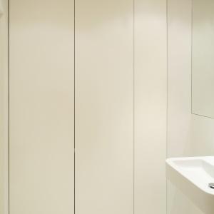 Po lewej stronie umywalki – za białymi drzwiczkami – jest schowana domowa pralnia. Fot. Bartosz Jarosz.