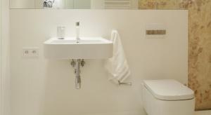 Na pierwszy rzut oka nie widać, że w tej eleganckiej łazience są pralka i suszarka. Schowano je we wnęce, za białymi drzwiczkami. Pojemna zabudowa meblowa sięga sufitu!