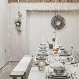 Urok tkwi w prostocie. Dlatego wśród świątecznych aranżacji stołu proponowanych przez producentów coraz częściej drewniany stół wychodzi na pierwszy plan. Tutaj idealnie harmonizuje z bardziej zdobną porcelaną oraz błyszczącymi świecznikami. Fot. Sainsbury Home.