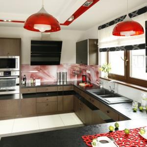 Ścianę nad blatem zdobi fototapeta kolorystyką nawiązująca do czerwonych dodatków w kuchni. Projekt: Marta Kilan. Fot. Bartosz Jarosz.