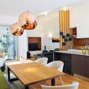 Słoweńscy architekci z pracowni GAO Arhitekti stworzyli nowoczesne i przytulne wnętrze. Otwartą strefę dzienną stanowi salon z jadalnią i kuchnią. Tę ostatnią od przestrzeni spożywania posiłków oddziela wyspa, pełniąca funkcję domowego baru. Projekt: Gao Arhitekti. Fot. Mateja Jordovič Potočnik.