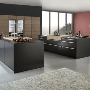 Nowość od niemieckiej firmy Leicht. Nowoczesna, elegancka kuchnia Bondi zachwyca pięknymi matowymi frontami w ciemnym, intensywnym kolorze. Aranżację ocieplają elementy w kolorze drewna - wysoka zabudowa i nakładane blaty. Fot. Leicht.