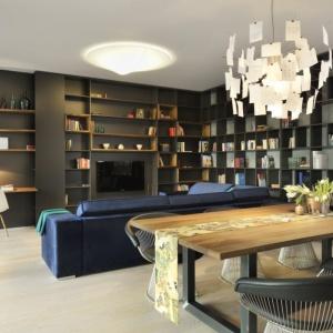 Ścianę w salonie zabudowano regałem, z wieloma mniejszymi półkami, które mogą posłużyć za biblioteczkę z imponującym zbiorem książek, jak również galerię porcelany. W rogu, przy wyjściu na taras, urządzono niewielką przestrzeń do pracy. Projekt: Biuro Architektoniczne GAO Arhitekti. Fot. Miran Kambic.