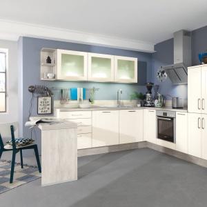 Jasne fronty mebli doskonale współgrają z kolorem niebieskim, którym pomalowano ściany. Niewielki bar zapewnia przyjemne miejsca na szybkie śniadanie lub poranną kawę. Na zdjęciu: meble z programu IP 4250 marki Impuls.