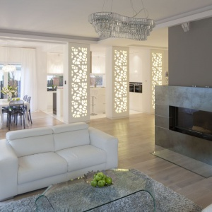 Elegancka i reprezentacyjna przestrzeń parteru jest otwarta. Ważny element dekoracyjny, decydujący o wyjątkowości wnętrza, stanowią filary z oryginalnymi, ażurowymi panelami, przez które sączy się ciepłe światło. Projekt: Katarzyna Mikulska-Sękalska. Fot. Bartosz Jarosz.