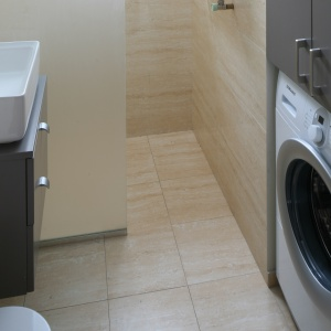Wnęka z pralką powstała po przebiciu ściany sypialni. Tafla szkła wydziela prysznic. Fot. Bartosz Jarosz.