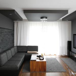 Nieduży salon urządzono w ciemnych szarościach. Ich elegancki charakter podkreśla kolor naturalnego drewna, które dodatkowo ociepla przestrzeń. Projekt: Michał Mikołajczak. Fot. Bartosz Jarosz.