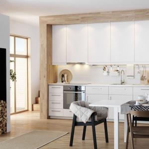 Biała zabudowa na jedną ścianę z wysokimi górnymi półkami jest w stanie pomieścić wszystkie potrzebne kuchenne sprzęty. Ociepla ją wizualnie drewniana podłoga oraz oryginalna drewniana rama, tworząca ciekawą wnękę, w którą wpasowano aneks. Fot. IKEA.