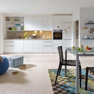 Biała zabudowa kuchenna na jedną ścianę oferuje wszystkie podstawowe funkcje, w tym otwarte i zamknięte górne szafki. Dodatkowe miejsce do przechowywania zyskujemy na ścianie, spajającej wizualnie kuchnię z jadalnią, a skandynawski klimat buduje podłoga z bielonego drewna oraz industrialne oświetlenie nad stołem. Fot. Schueller.