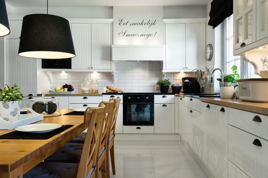 W tej kuchni skandynawski klimat zauważalny jest już za sprawą dwujęzycznego napisu na obudowie okapu kuchennego (w języku polskim i szwedzkim). Oprócz tego, w atmosferę tę wpisują się również białe meble z delikatnymi frezowaniami, czarne dodatki dekoracyjne oraz drewniany blat. Fot. Pracownia Mebli Vigo.