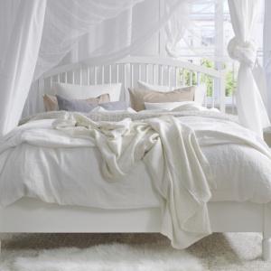 Białe łóżko można połączyć z każdym kolorem tkanin, jeśli jednak chcemy stworzyć aranżację w stylu skandynawskim, zestawmy je z narzutą w bieli, przełamaną delikatnymi, pastelowymi poduchami. Fot. IKEA.