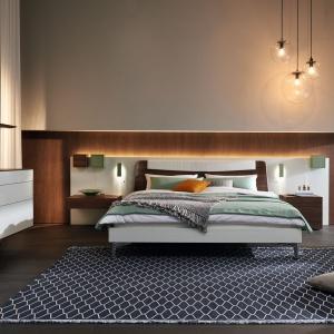 Łóżko w kolekcji Lunis zintegrowane jest z dużym panelem, do którego zamontowano półki nocne, ale i lampki. Całość tworzy komfortowy i funkcjonalny mebel. Fot. Hulsta.