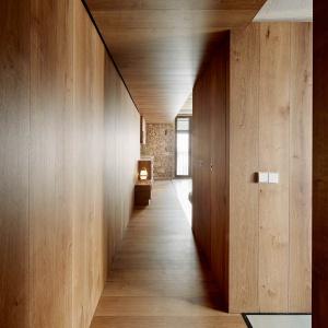 Korytarze wyścieła drewniana okładzina nadając przytulny charakter nawet takiemu elementowi wnętrza jak ciągi komunikacyjne. Projekt: MESURA, Partners in Architecture. Fot. José Hevia.