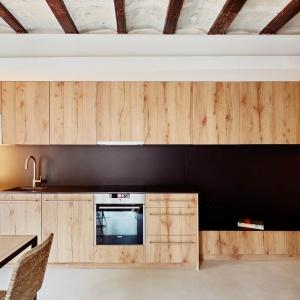 W przestrzeni tego apartamentu ścianę nad blatem zaakcentowano satynową czernią, pięknie kontrastującą z drewnianą zabudową. Projekt: MESURA, Partners in Architecture. Fot. José Hevia.