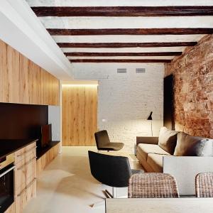 Obecność mocnej barwy we wnętrzu łagodzi biała ściana łącząca przestrzeń wypoczynku z aneksem kuchennym. Aby jednak nie było zbyt sterylnie, pod białą farbą kryje się szorstka faktura cegły. Projekt: MESURA, Partners in Architecture. Fot. José Hevia.
