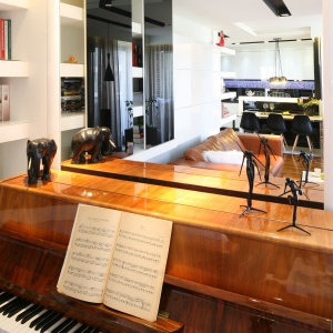 Zamontowane na całej ścianie lustro, przy którym ustawiono pianino, optycznie dubluje niedużą przestrzeń. Projekt: Małgorzata Mazur. Fot. Bartosz Jarosz.