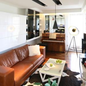W niedużym apartamencie znalazło się sporo miejsca na przechowywanie, ale też pianino. Szklane i lakierowane na wysoki połysk powierzchnie optycznie powiększają przestrzeń. Projekt: Małgorzata Mazur. Fot. Bartosz Jarosz.