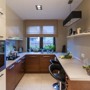 Ściany w kuchni mają delikatny szary odcień i stanowią idealne tło dla dwukolorowej zabudowy kuchennej. Dolną jej część utrzymano w kolorze drewna, a lekkości meblom dodają fronty w kolorze złamanej bieli. Projekt i zdjęcia: Gabinet wnętrz.