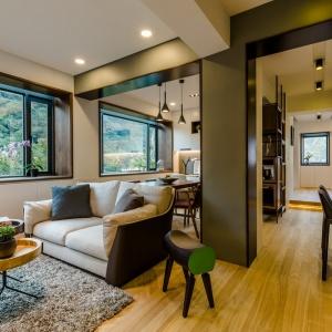 Tajwańska pracownia Archlin Studio podjęła się renowacji starego domu, w którym wprowadziła do wnętrz dużo światła oraz postawiła na przytulne kolory ziemi. W strefie dziennej naturalne drewno połączono z szarościami. Projekt i zdjęcia: Archlin Studio.