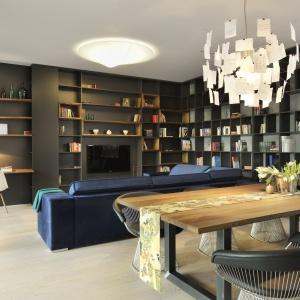 Słoweńskie biuro Gao Arhitekti zaprojektowało eklektyczne wnętrze z dużą dozą industrialnego klimatu, które mimo to jest przytulne. Różne odcienie szarości połączono z drewnianymi akcentami - blatem stołu jadalnianego oraz półkami, wbudowanymi w ciekawie zorganizowaną zabudowę, pełniącą funkcję biblioteczki. Projekt: Gao Arhitekti. Fot. Miran Kambic.