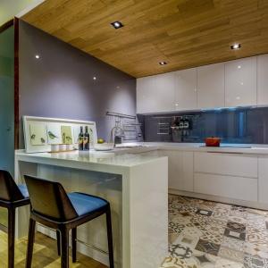 W kuchni ciekawym rozwiązaniem jest wykończenie drewnem... sufitu. Dzięki białej zabudowie w wysokim połysku nie przytłacza ona aranżacji wnętrza. Podłogę zdobią patchworkowe płytki w różnych odcieniach szarobrązowego koloru. Projekt i zdjęcia: Archlin Studio.
