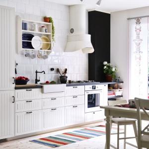 Biała zabudowa na jedną ścianę zachwyca subtelnym, pionowym frezowaniem oraz mocno zaznaczonymi czarnymi uchwytami. Oprócz zdobnych frontów prowansalski klimat buduje klasyczny, lekko rustykalny okap, angielski zlewozmywak oraz stylizowana bateria. Fot. IKEA.