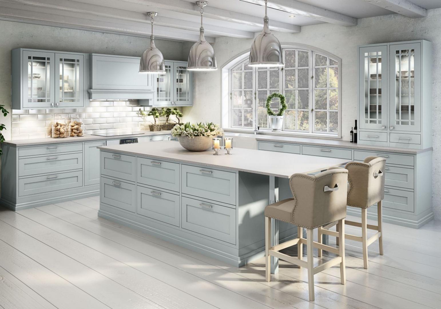 Delikatnie frezowane fronty mebli kuchennych mają kolor wyblakłego błękitu - klasycznej barwy typowej dla prowansalskich kuchni. Przytulny klimat budują również przeszklone szafki górne, dodatkowo zwieńczone ozdobnymi szprosami. Fot. Sigdal.